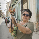 Woman and Small Dog in Havana, Cuba. A female resident in old Havana, Cuba holds up her small dog to be photographed Stock Images