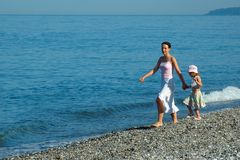 Woman with small girl. Go on seaside Royalty Free Stock Images