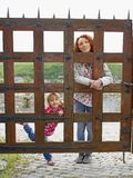 Woman and a small girl behind a wooden gate Stock Photography