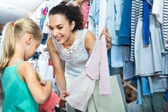 Woman with small girl choosing pink clothes Royalty Free Stock Images