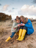 Woman and small girl playing together in dune landscape Stock Images