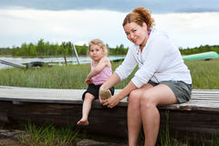 Woman and small kid near a river Stock Photos