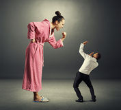 Woman and small man. Angry women in pink dressing gown screaming at small startled men in the dark room Royalty Free Stock Photo
