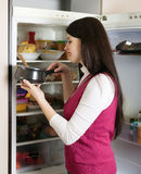 Woman with small pan near opened refrigerator Royalty Free Stock Photos