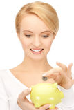 Woman with small piggy bank and coin Stock Images