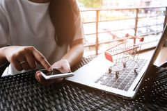 Woman and Small shopping cart with Laptop for Internet online sh stock photos