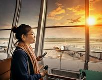 Woman with smart phone in hand standing in airport terminal building and airliner plane departure on runway royalty free stock image