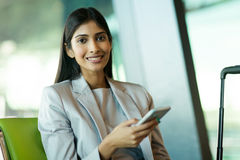 Woman smart phone. Happy young indian woman using smart phone while waiting for her flight Stock Photography