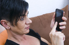 Woman with smart phone. Head-and-shoulder view from elevated camera position of a black-haired woman of middle age on brown sofa sitting and Smartphone typing Royalty Free Stock Image