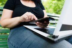 Woman with smart phone and laptop working outdoors royalty free stock images