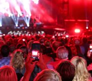 Woman with smart phone at live concert. Young woman with smart phone at live concert and many people royalty free stock photo
