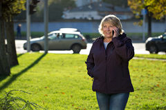 Woman with smart phone outdoors in autumn Royalty Free Stock Photos