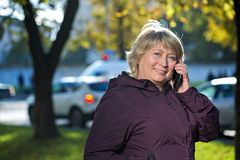 Woman with smart phone outdoors in autumn Royalty Free Stock Photography
