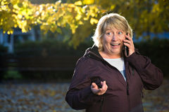 Woman with smart phone outdoors in autumn Stock Image