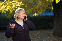 Woman with smart phone outdoors in autumn Royalty Free Stock Image