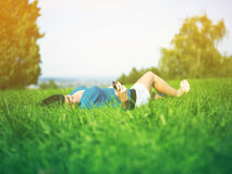 Woman with smart phone in park, on green grass Royalty Free Stock Photography