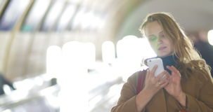 Woman with smart phone on subway escalator. Young blonde woman riding on escalator in underground and using smart phone. urban lifestyle, keeping in touch every stock footage