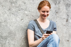 Woman with Smartphone Against a Wall Stock Photography