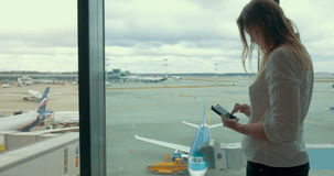 Woman with Smartphone in Airport. Young woman is typing a message in smartphone standing by the airport window. Aircraft parking area is on the background stock video