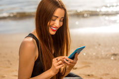 Woman with smartphone on the beach. Young woman in black sport clothes using smartphone on the sandy beach Royalty Free Stock Image