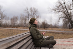 Woman with smartphone on a bench Royalty Free Stock Photo