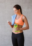 Woman with smartphone and bottle of water in gym Royalty Free Stock Images