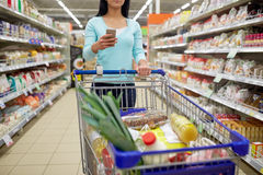 Woman with smartphone buying food at supermarket Royalty Free Stock Image