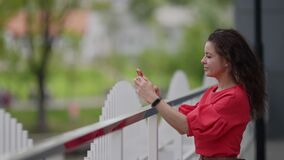 woman with smartphone in city, taking selfie by frontal camera of mobile phone