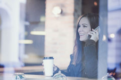 Woman with smartphone drinking coffee. Royalty Free Stock Photos