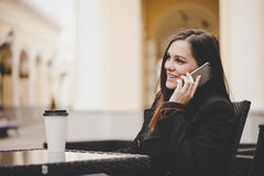 Woman with smartphone drinking coffee. Stock Photography