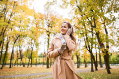 Woman with smartphone and earphones in autumn park Royalty Free Stock Images
