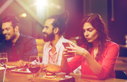 Woman with smartphone and friends at restaurant. Leisure, technology, internet addiction, lifestyle and people concept - women with smartphone and friends at Stock Photos
