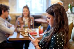 Woman with smartphone and friends at restaurant Stock Image