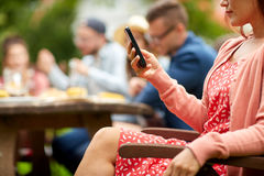 Woman with smartphone and friends at summer party Royalty Free Stock Images