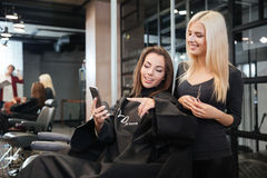 Woman with smartphone and hairdresser making hair styling at salon Stock Images