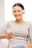 Woman with smartphone and headphones at home Stock Photography