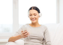 Woman with smartphone and headphones at home royalty free stock image