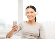 Woman with smartphone and headphones at home Royalty Free Stock Images