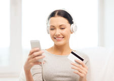 Woman with smartphone and headphones at home Royalty Free Stock Photos
