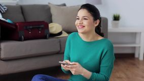 Woman with smartphone at home going to travel. Tourism, travel, people, technology and communication concept - happy young woman going on trip and texting on stock video footage