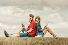 Woman with smartphone man with tablet couple outdoor Royalty Free Stock Image