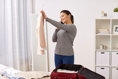 Woman with smartphone packing travel bag at home Royalty Free Stock Photo