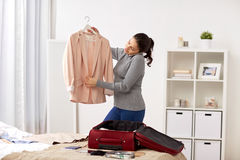 Woman with smartphone packing travel bag at home Stock Images