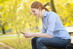 Woman with Smartphone in a Park Royalty Free Stock Photography