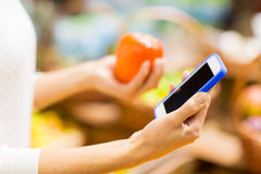 Woman with smartphone and persimmon in market. Sale, shopping, consumerism and people concept - close up of young woman hands with smartphone and persimmon in Royalty Free Stock Photography