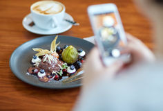 Woman with smartphone photographing food at cafe Stock Photo