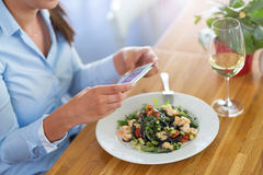 Woman with smartphone photographing food at cafe Stock Images