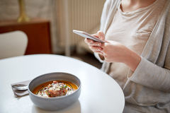 Woman with smartphone and pumpkin soup at cafe Royalty Free Stock Image