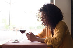 Woman with smartphone in restaurant Stock Photo