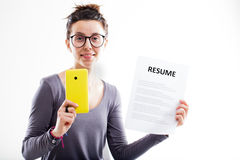 Woman with smartphone and a resume Stock Image